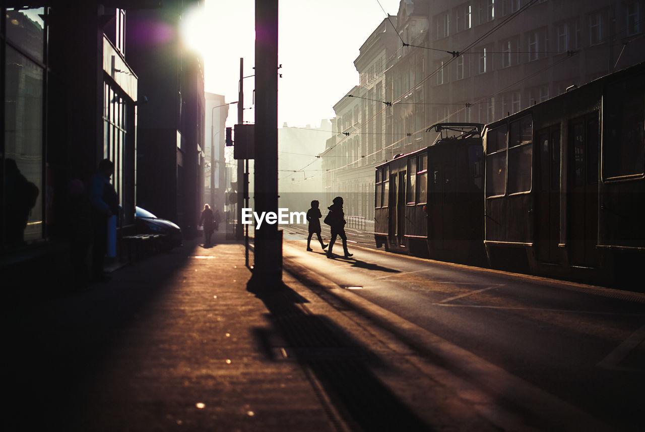 Silhouette Women Walking By Tram On Street Amidst Buildings In City