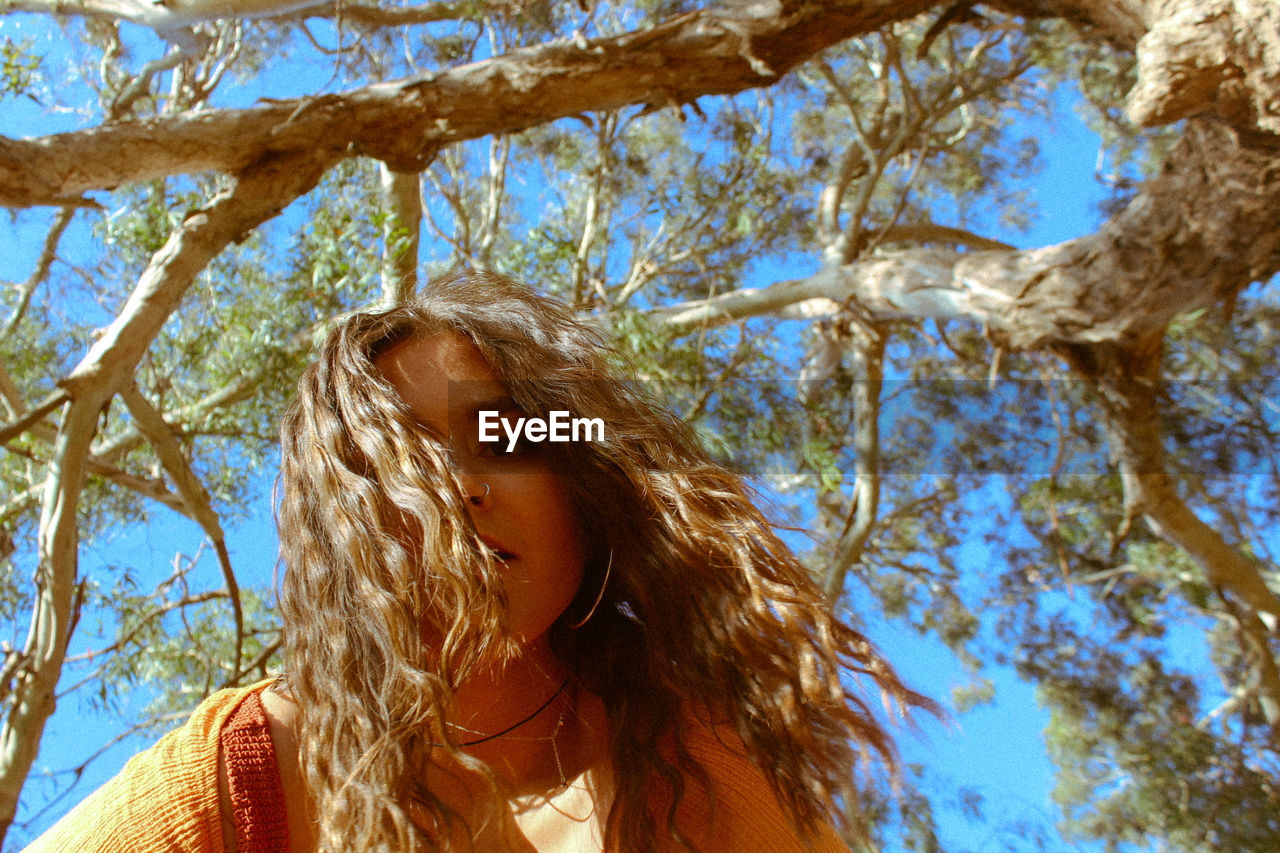 Low angle portrait of young woman with long hair against tree