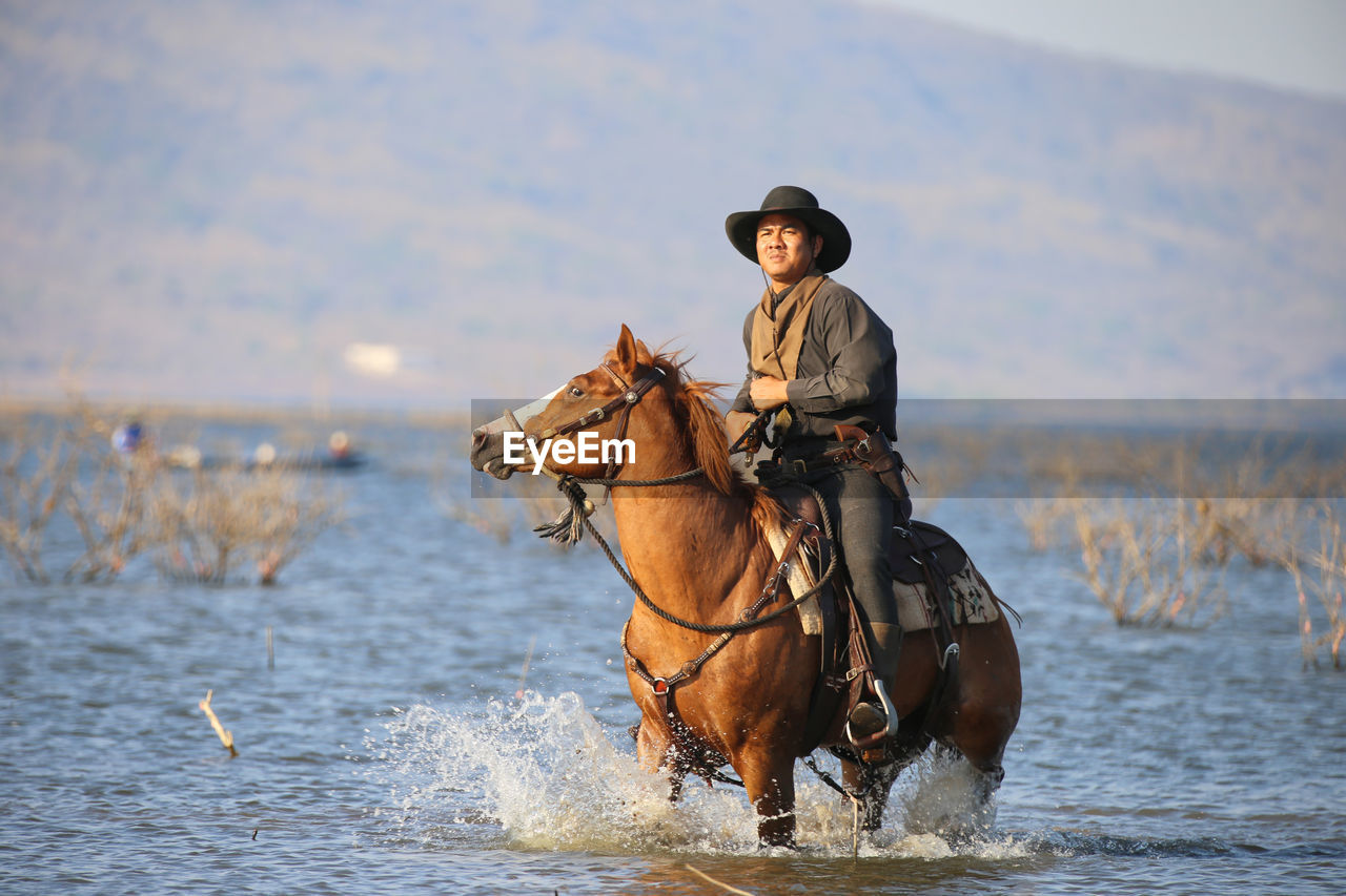 water, real people, mammal, domestic animals, animal themes, domestic, one person, animal, horse, pets, hat, animal wildlife, livestock, sea, vertebrate, leisure activity, lifestyles, one animal, nature, riding, outdoors, cowboy hat, mature men