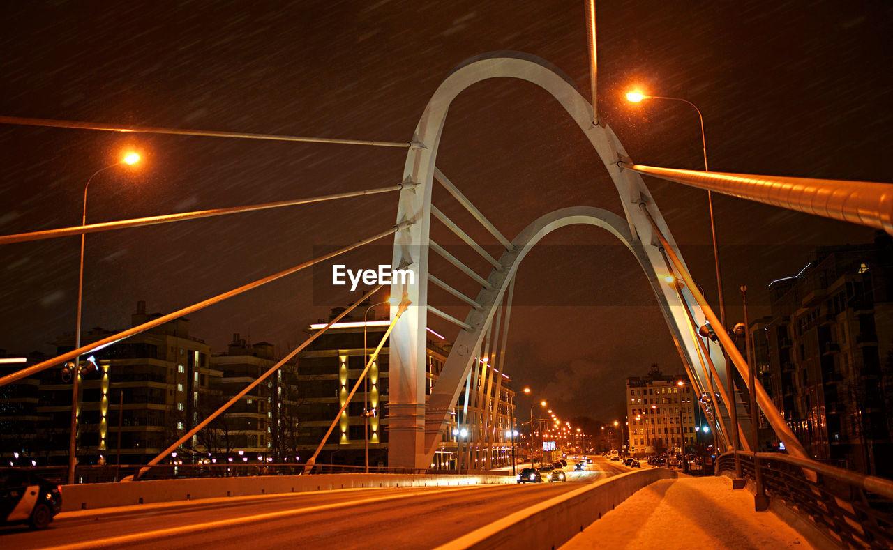 ILLUMINATED LIGHT TRAILS ON BRIDGE AT NIGHT