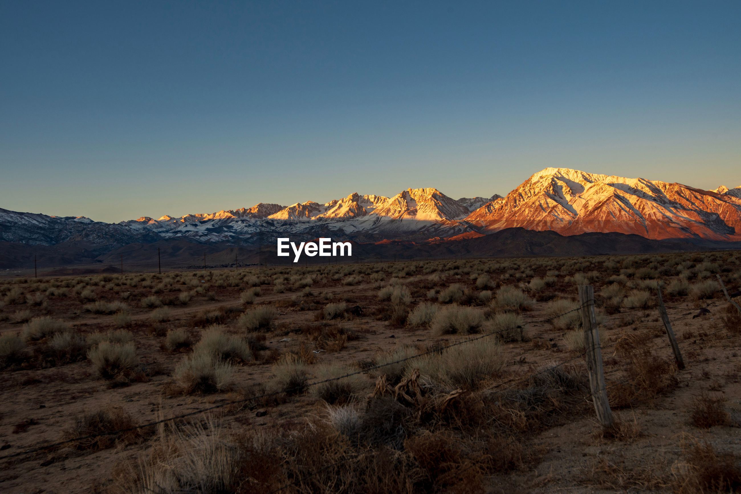 Scenic view of arid landscape at sunrise with snowy mountains against clear sky