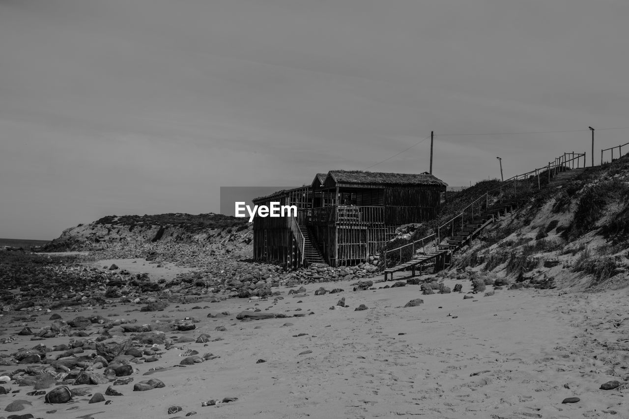 built structure, architecture, sky, land, building exterior, nature, building, no people, beach, day, sand, snow, cold temperature, abandoned, house, non-urban scene, outdoors, winter, tranquil scene