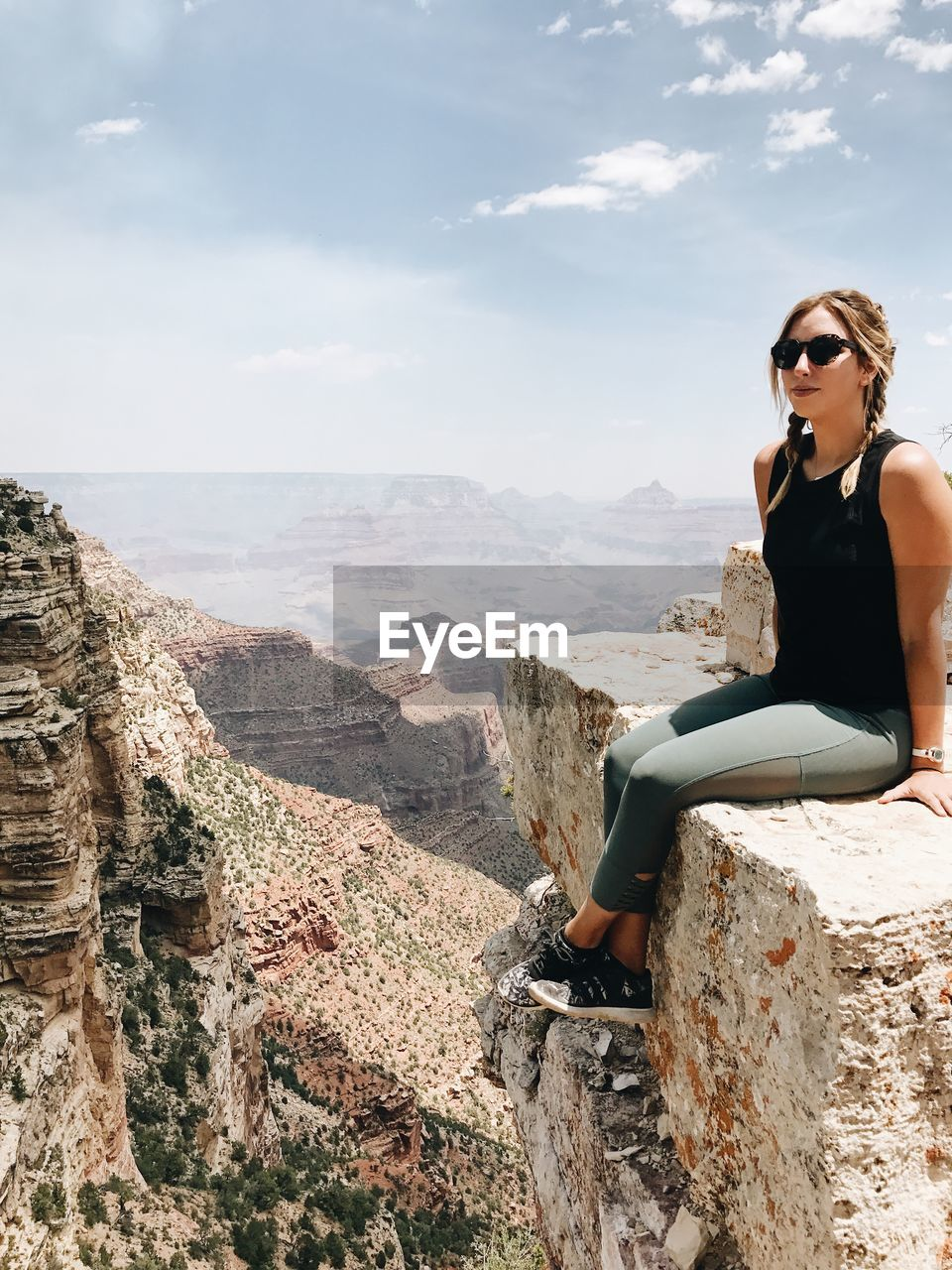 Portrait Of Woman Sitting On Cliff Against Sky