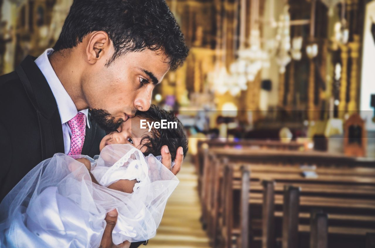 Young Man Kissing Baby Girl On Forehead In Church