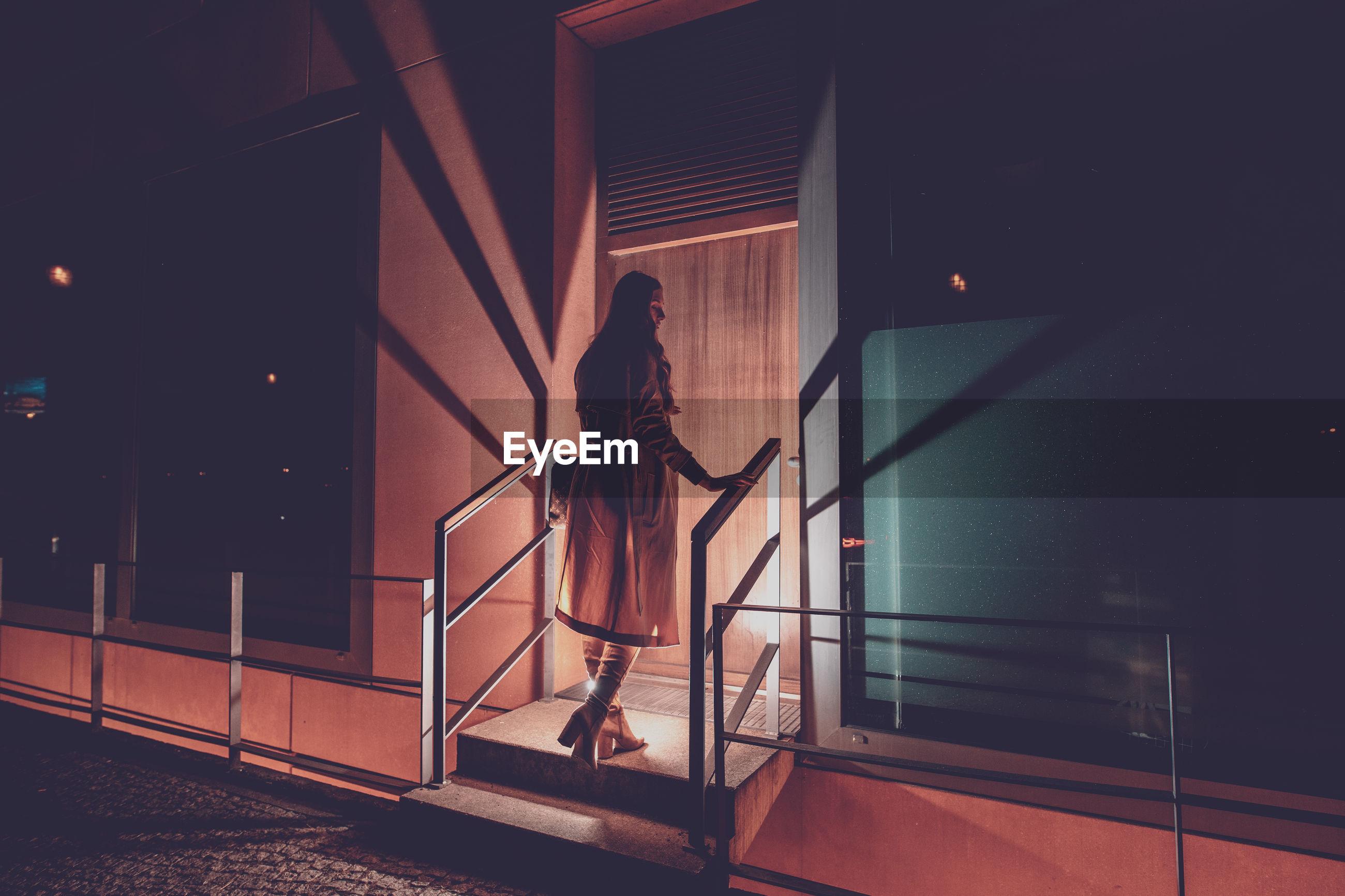 Rear view of woman walking towards entrance at night