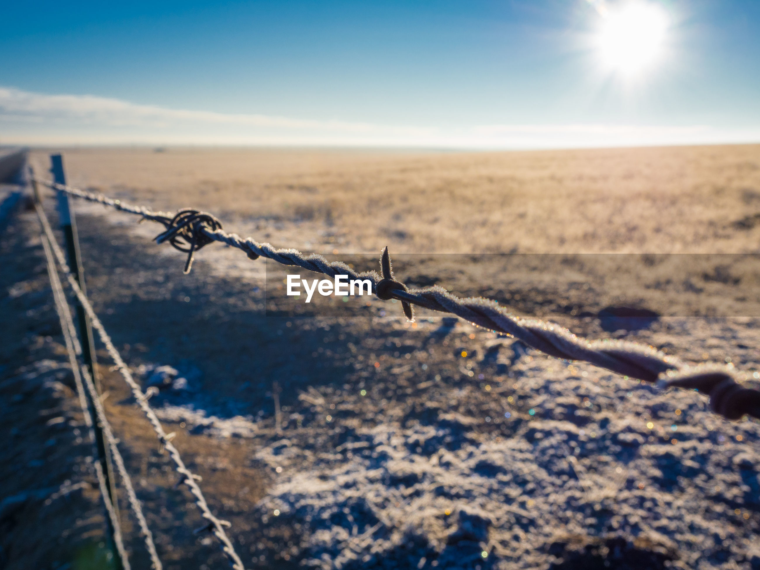 Close-up of frosted barbed wire fence on field against sky