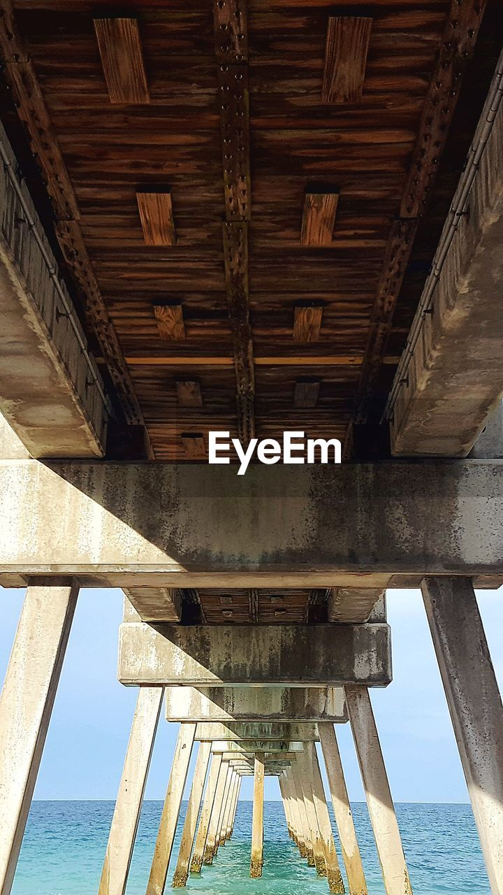 architecture, built structure, underneath, wood - material, bridge, connection, water, below, no people, low angle view, sea, bridge - man made structure, day, nature, beach, outdoors, architectural column, land, pier, ceiling