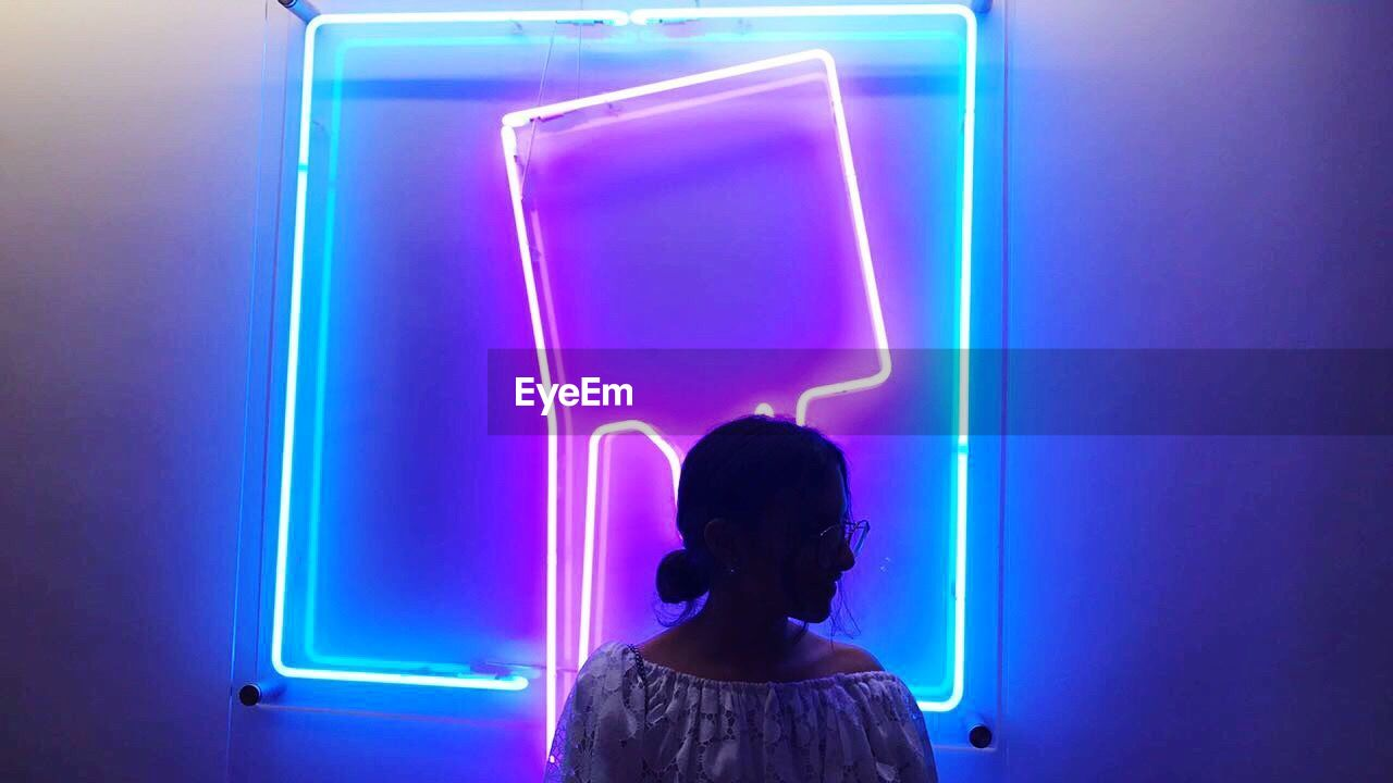 rear view, childhood, illuminated, technology, one person, children only, child, night, real people, indoors, girls, blue, multi colored, people, neon, adult