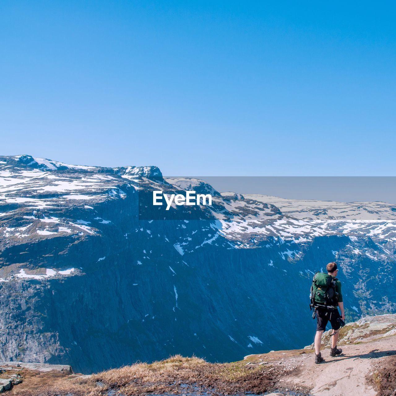 Man on mountain against clear blue sky
