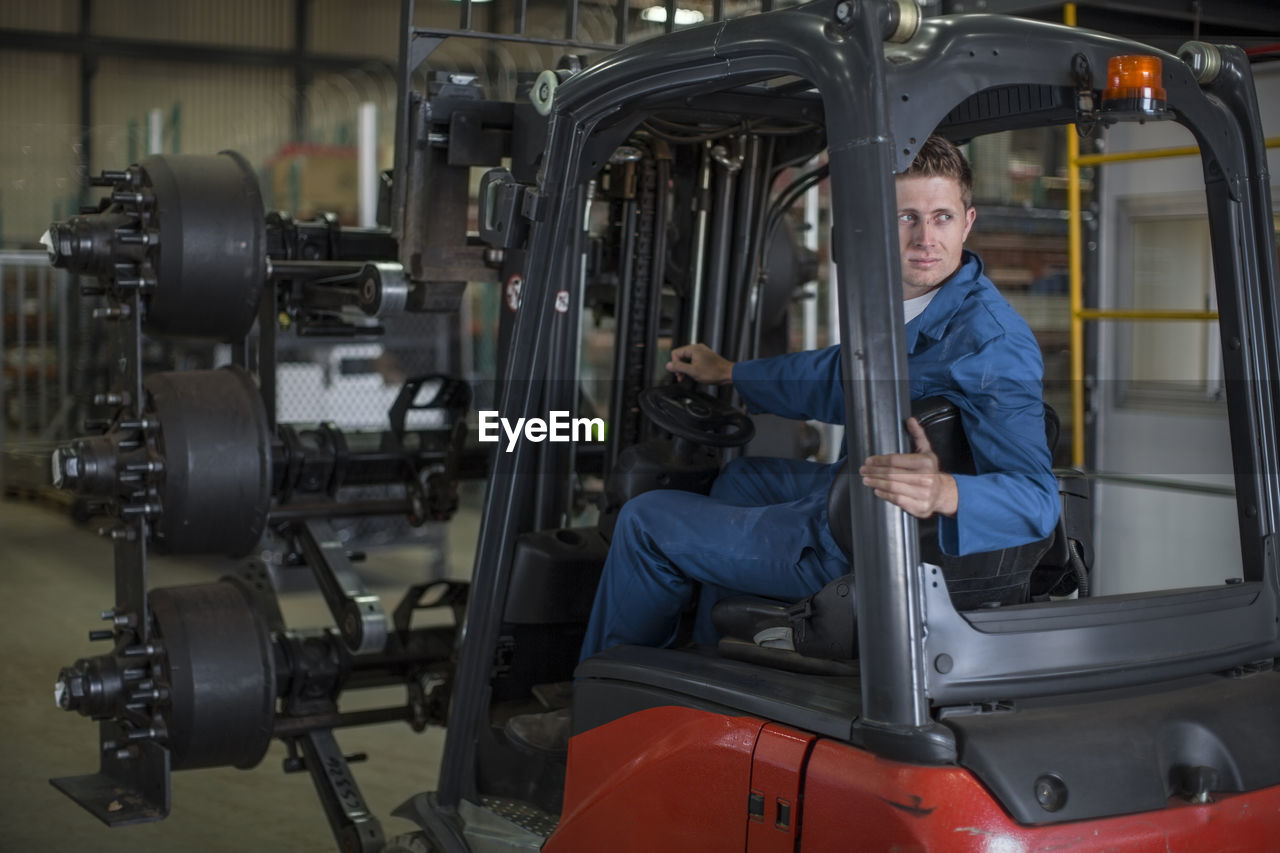FULL LENGTH PORTRAIT OF A MAN HOLDING MACHINE