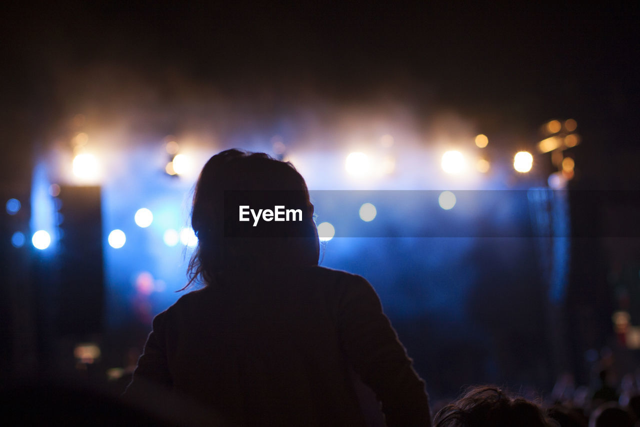 Rear view of woman at music concert