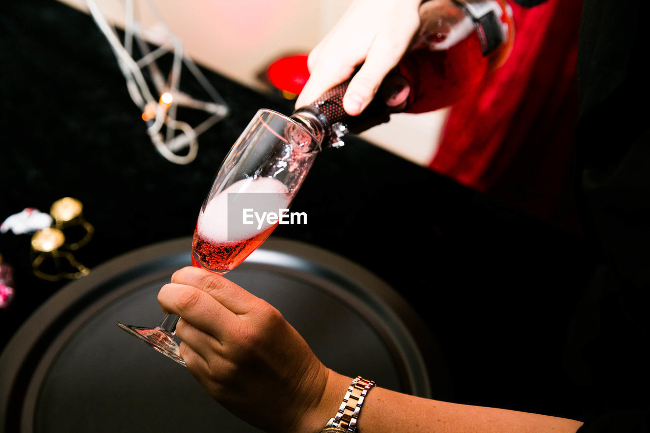 human hand, hand, real people, holding, one person, human body part, food and drink, lifestyles, indoors, alcohol, refreshment, drink, glass, wine, unrecognizable person, focus on foreground, pouring, midsection, women, finger, red wine