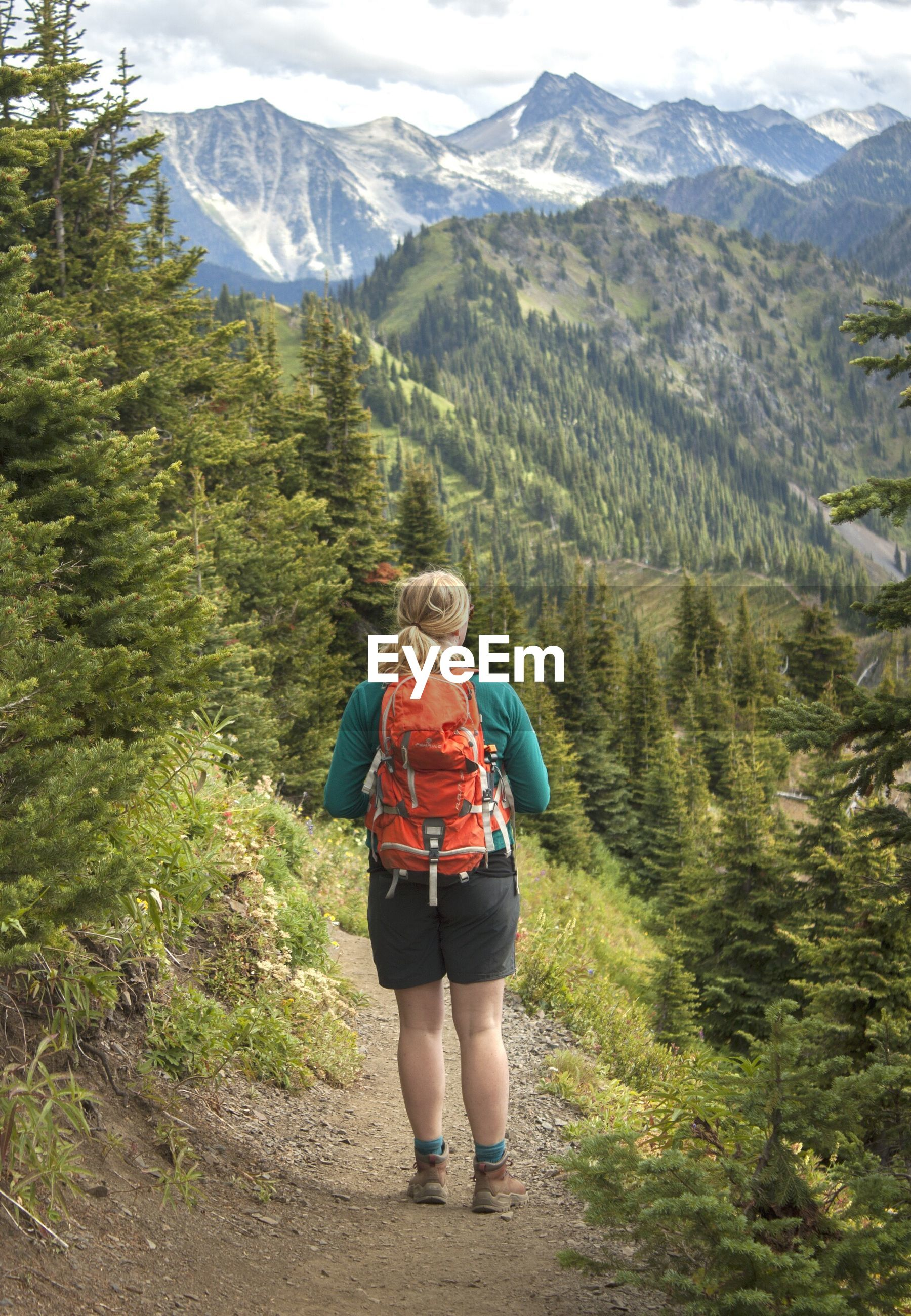 Rear view full length of backpack hiker standing against mountains