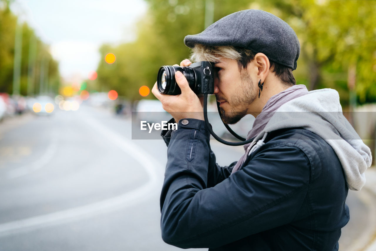 Side view of man photographing with camera in city