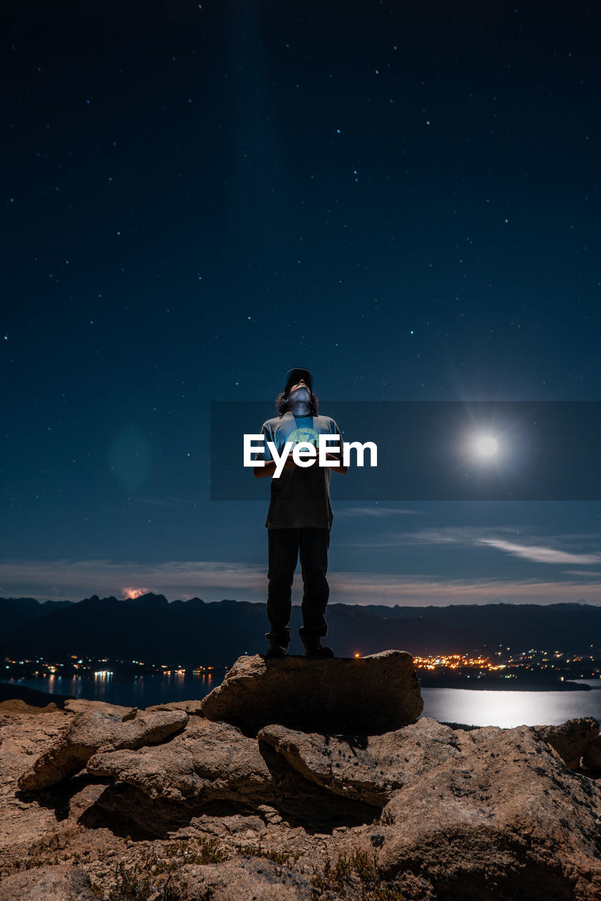 Full length of man operating drone while standing on rock against sky at night