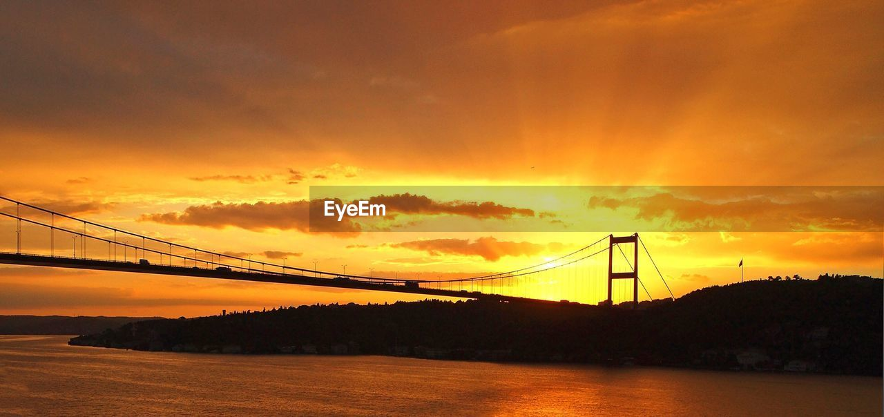 Fatih sultan mehmet bridge over river against cloudy sky during sunset