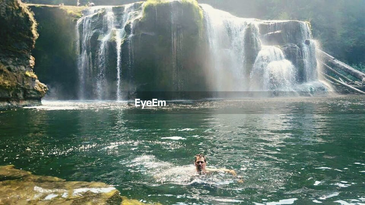 waterfall, water, motion, vacations, adventure, nature, splashing, rock - object, travel, scenics, beauty in nature, one person, outdoors, travel destinations, day, mountain, cliff, lifestyles, sea, swimming, people, power in nature, adults only, young adult, adult, sky