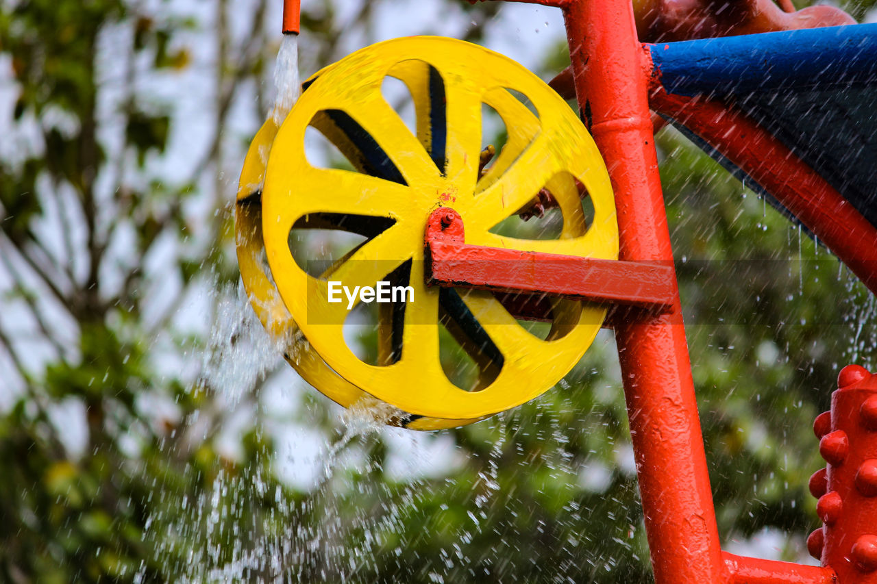 yellow, focus on foreground, day, motion, water, nature, no people, outdoors, multi colored, close-up, selective focus, plant, red, geometric shape, orange color, shape, circle, wheel