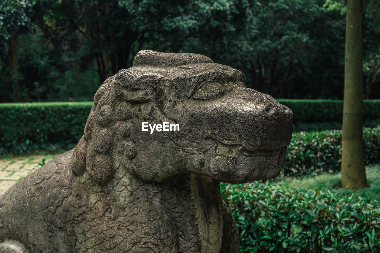 Close-up of sitting kylin statue against trees in park