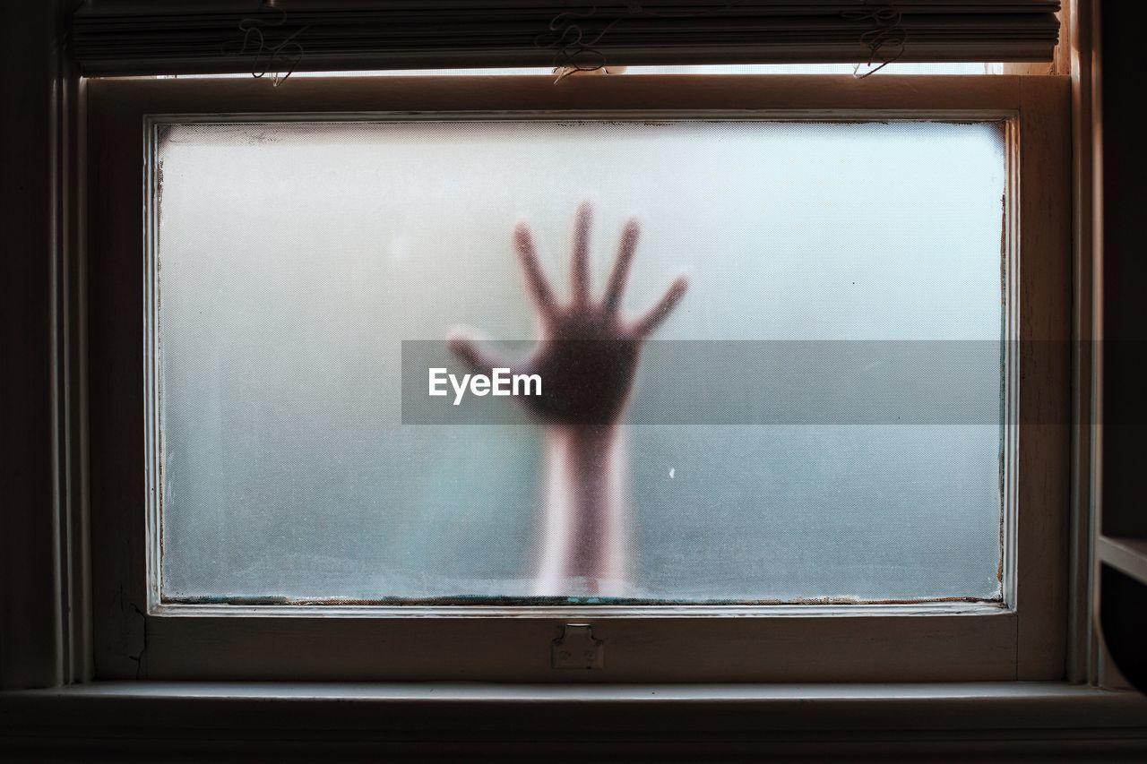 Cropped Hand Seen Through Bathroom Window