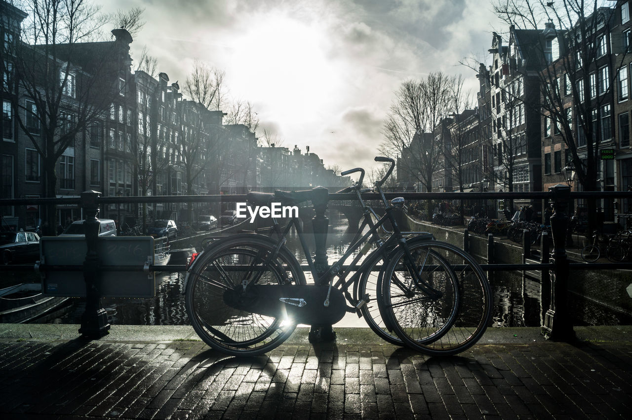 bicycle, building exterior, transportation, architecture, land vehicle, built structure, mode of transport, outdoors, city, day, real people, tree, stationary, bare tree, men, sky, one person