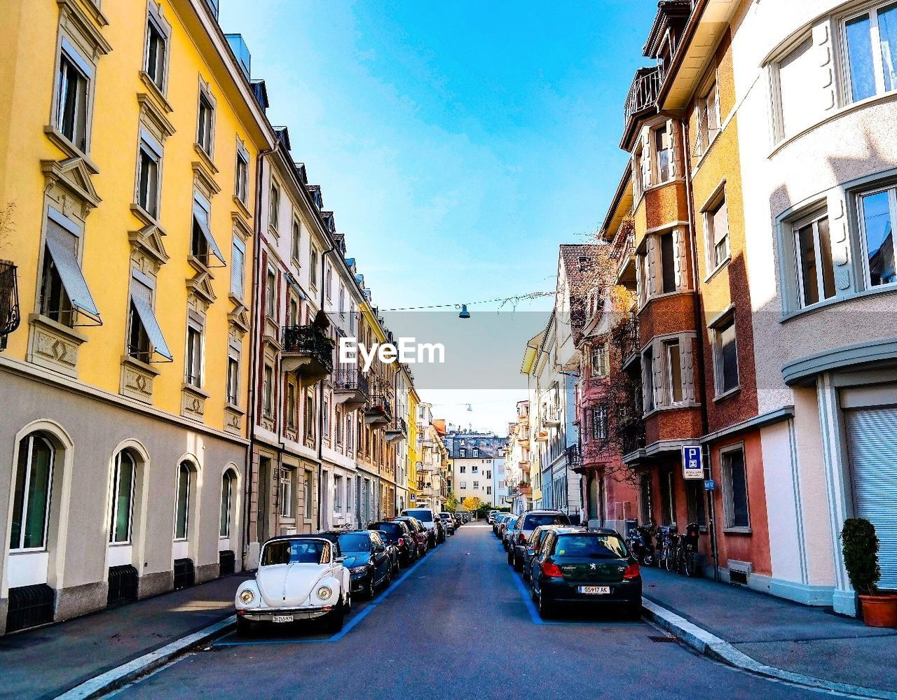 building exterior, architecture, car, built structure, street, transportation, window, city, land vehicle, mode of transport, sky, day, outdoors, road, residential building, the way forward, no people