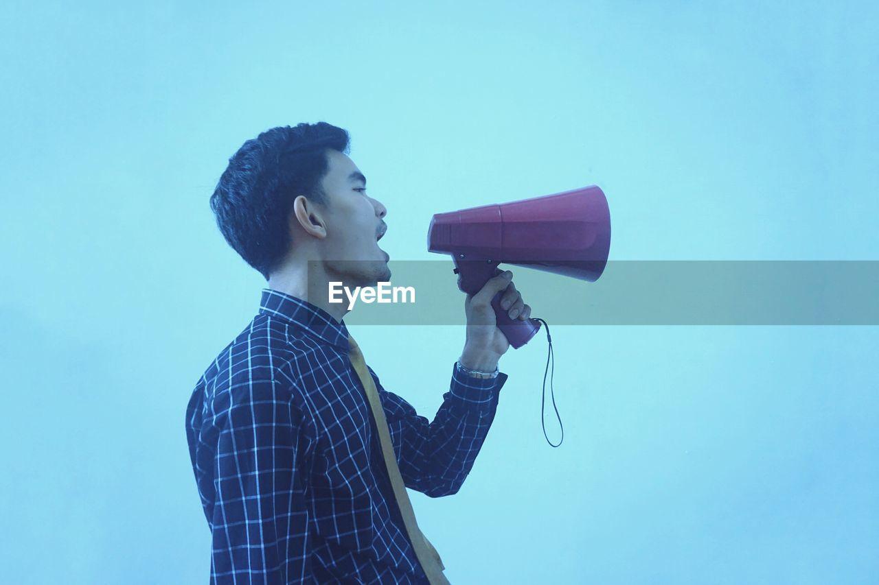 Man Speaking On Megaphone Against Blue Background