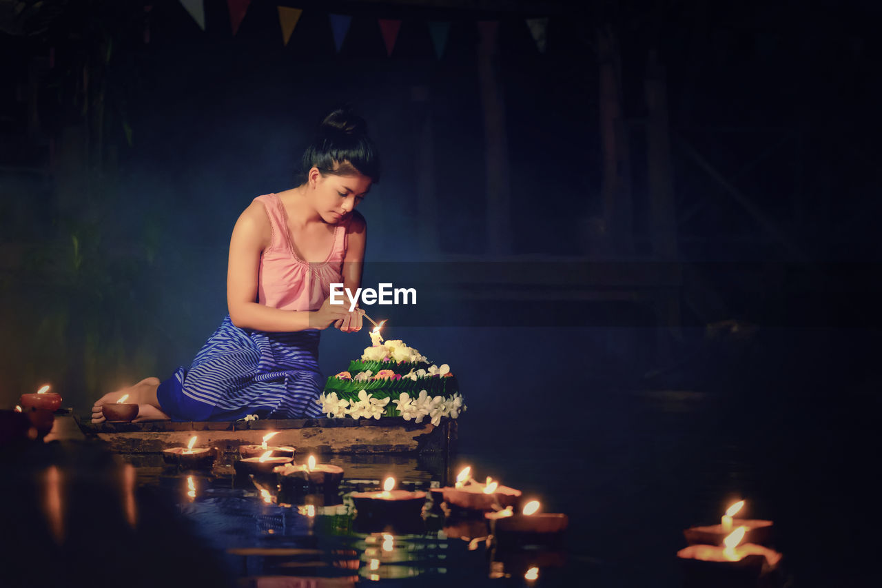 Young Woman Burning Incense Sticks By Diyas Floating On Pond
