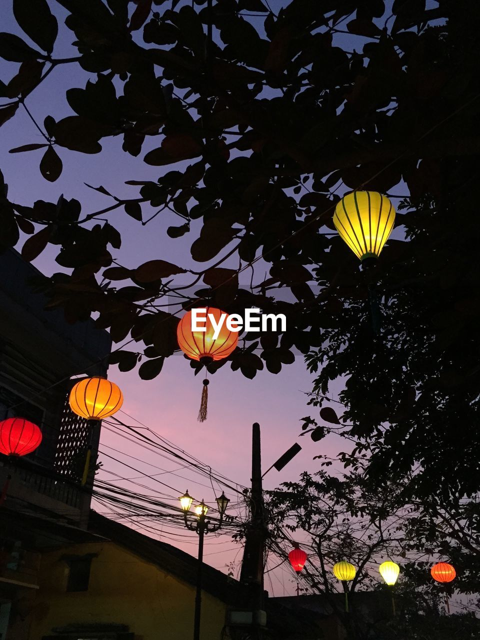 Low angle view of illuminated lanterns during sunset