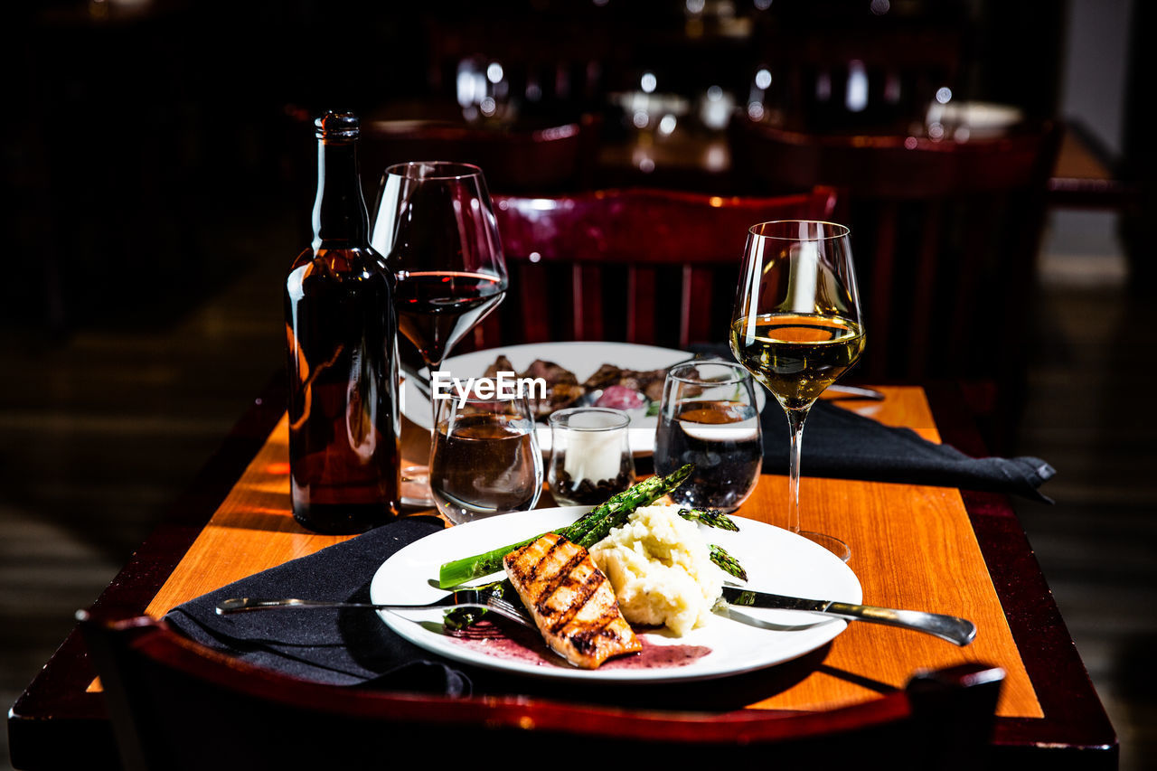 food and drink, table, refreshment, drink, alcohol, glass, freshness, plate, food, wine, indoors, red wine, ready-to-eat, wineglass, business, focus on foreground, still life, restaurant, no people, drinking glass, dinner, setting