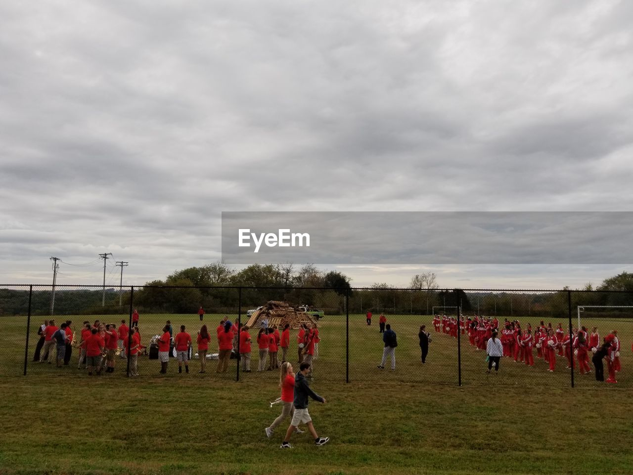 large group of people, cloud - sky, sport, field, competitive sport, real people, sky, men, sports clothing, team sport, playing, sports team, sports uniform, playing field, competition, togetherness, teamwork, exercising, lifestyles, leisure activity, outdoors, grass, day, soccer player, nature, adult, people