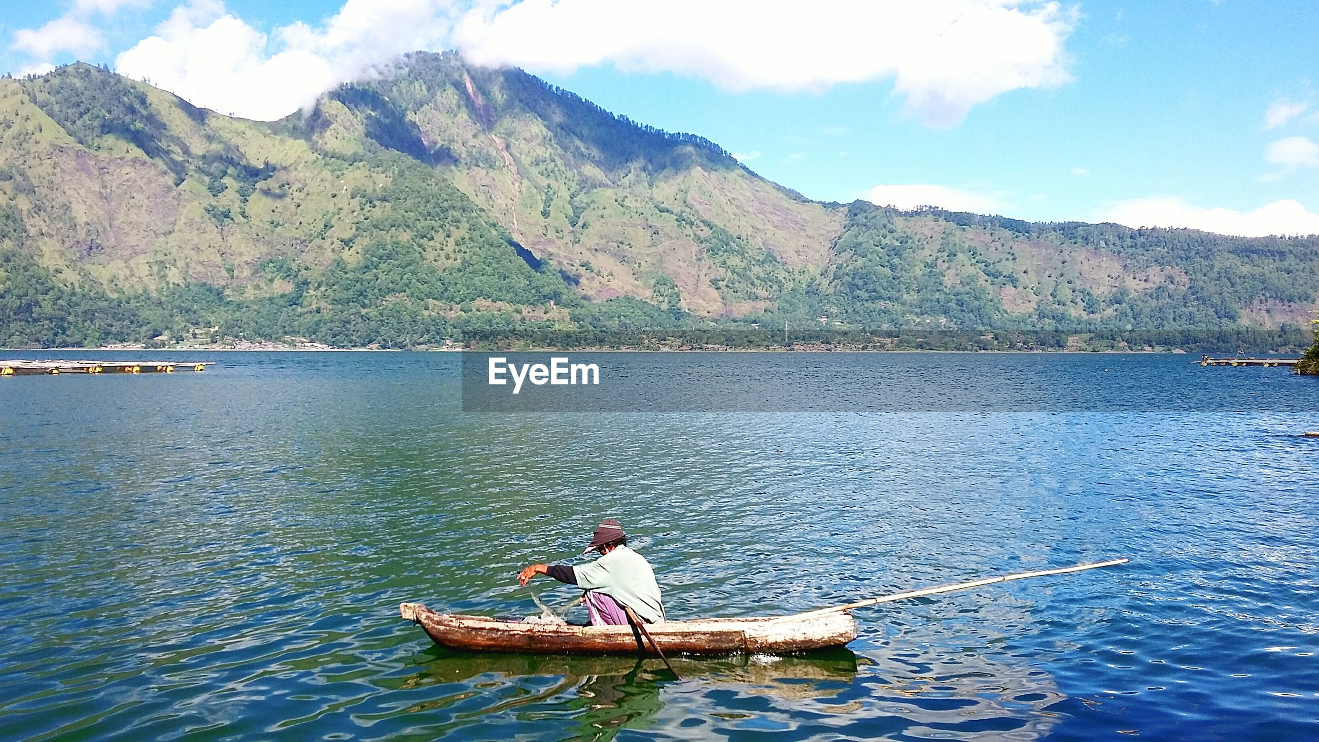 real people, mountain, day, water, transportation, nautical vessel, nature, outdoors, mode of transport, one person, waterfront, beauty in nature, scenics, sky, river, wooden raft, mountain range, men, cloud - sky, oar, fisherman, sitting, tree, full length, rowing, sailing, outrigger, people