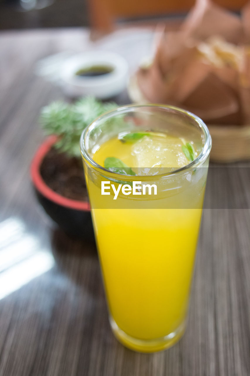 table, drink, food and drink, freshness, refreshment, drinking glass, indoors, yellow, focus on foreground, close-up, healthy eating, no people, day, food
