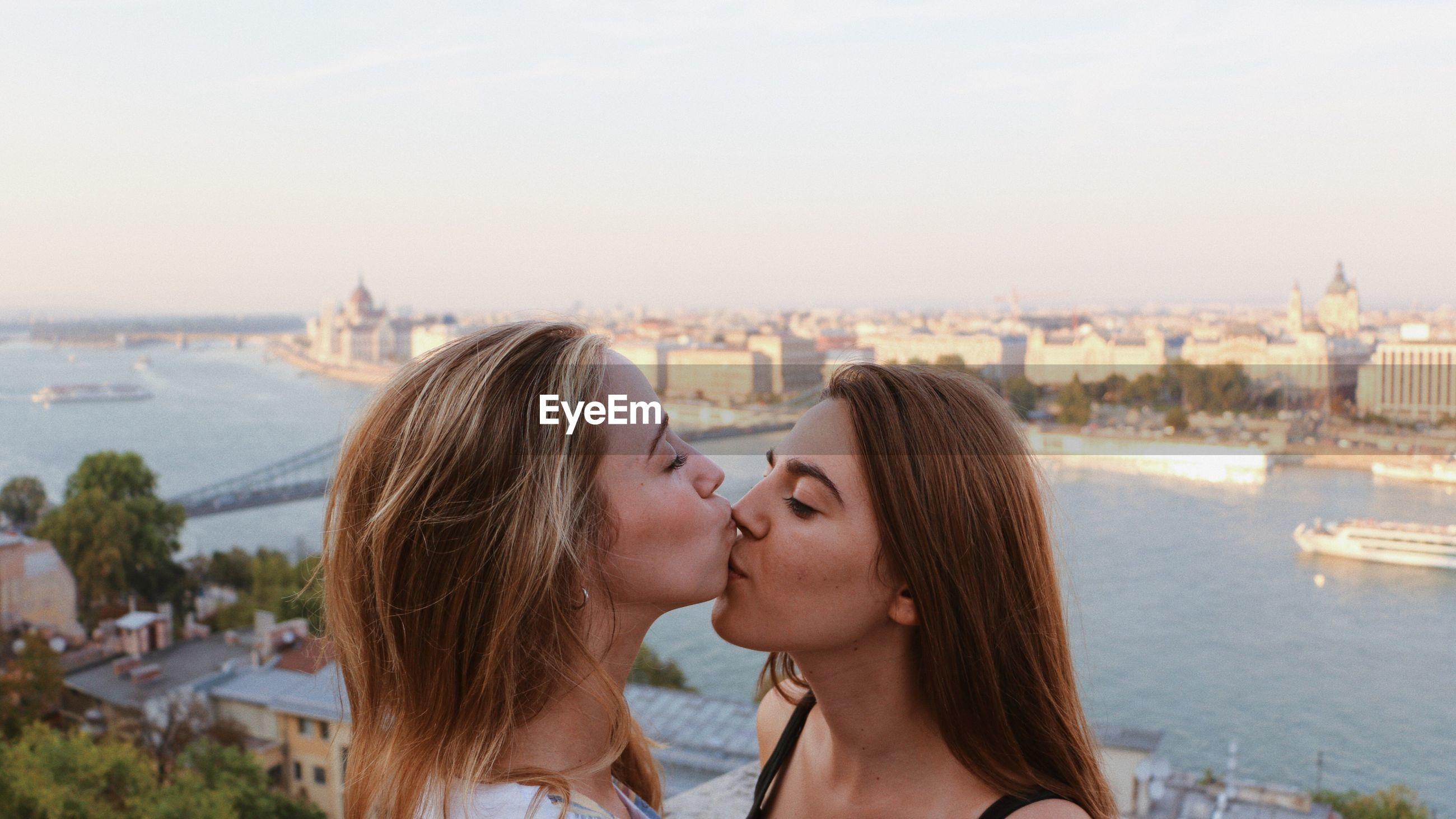 Lesbian couple kissing against cityscape