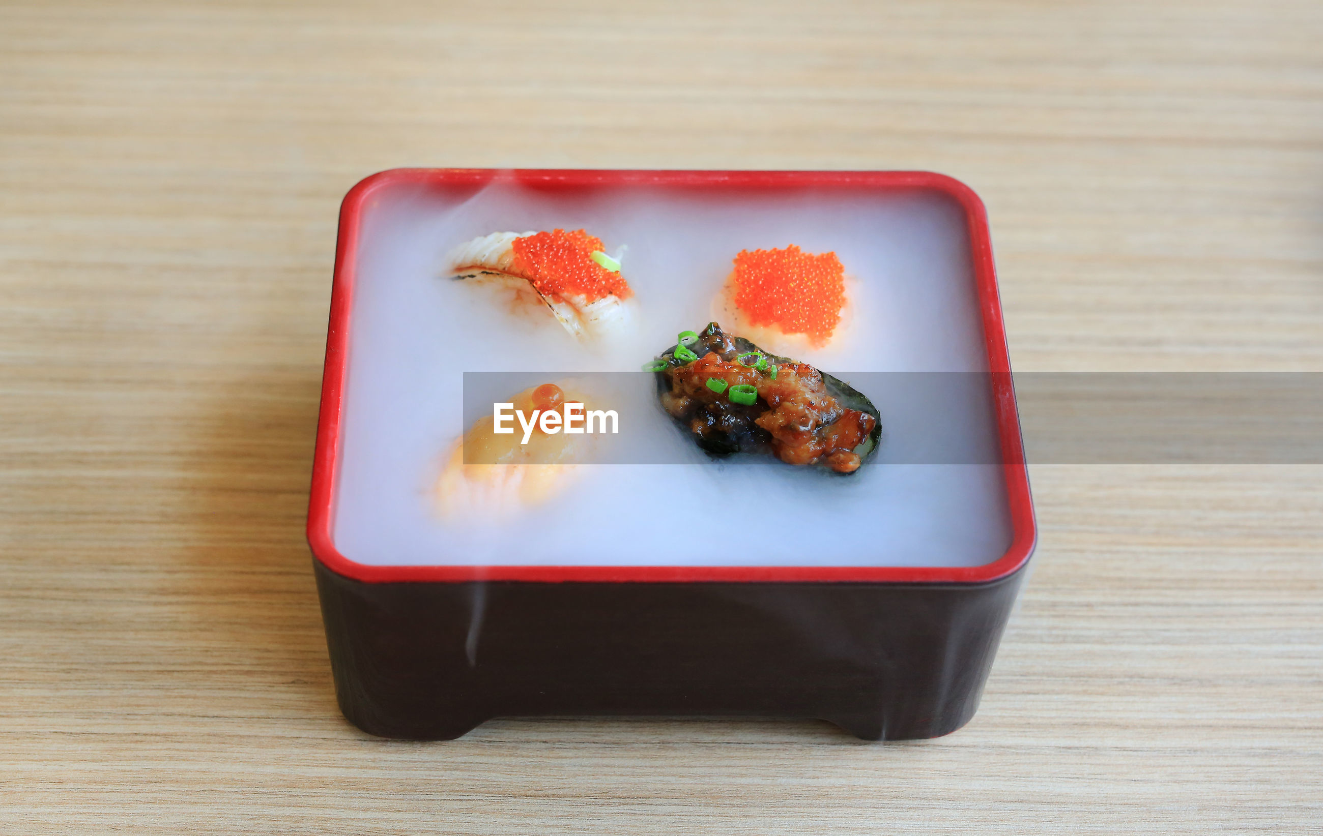 HIGH ANGLE VIEW OF SUSHI IN TRAY ON TABLE