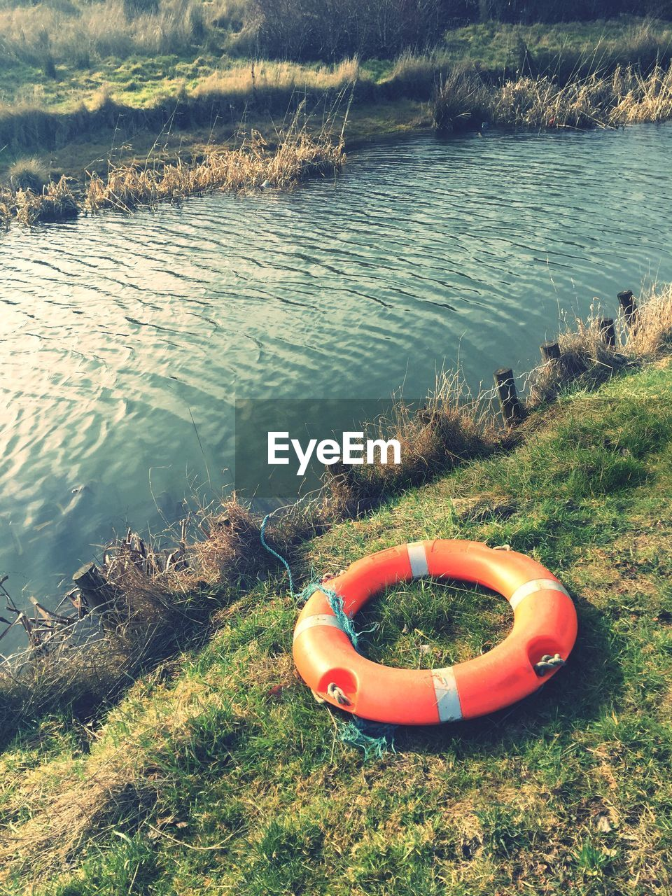 water, no people, nature, day, tranquility, lake, safety, protection, orange color, plant, inflatable, tranquil scene, life belt, security, tube, beauty in nature, grass, outdoors