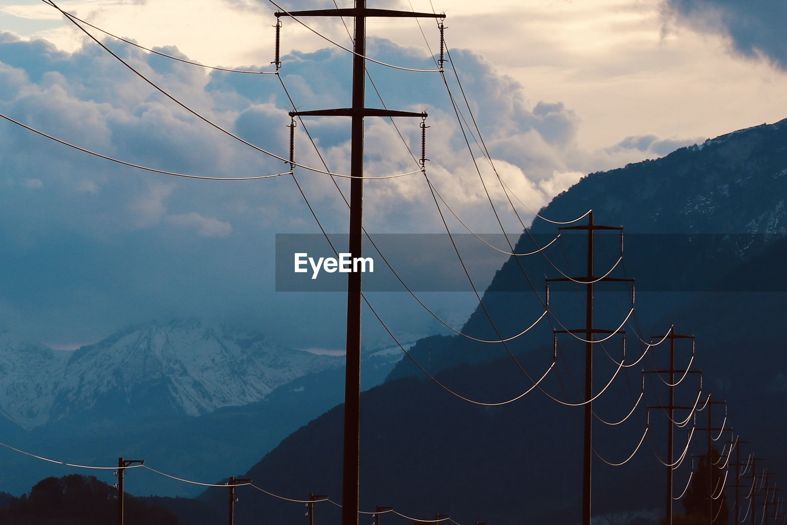 ELECTRICITY PYLON BY SNOWCAPPED MOUNTAINS AGAINST SKY DURING WINTER