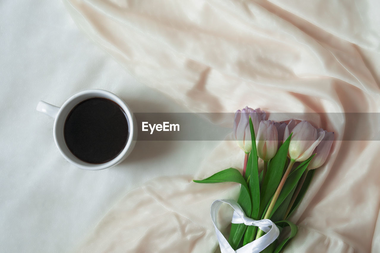 HIGH ANGLE VIEW OF COFFEE AND WHITE ROSES ON TABLE