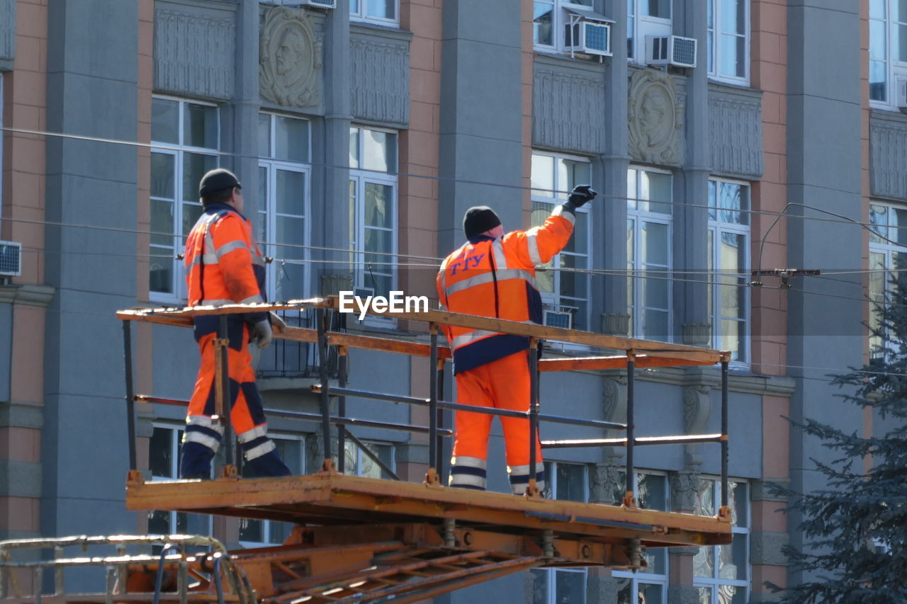 occupation, working, real people, men, built structure, reflective clothing, architecture, clothing, day, building exterior, group of people, orange color, construction worker, standing, safety, people, rear view, protective workwear, construction industry, outdoors, uniform, coworker