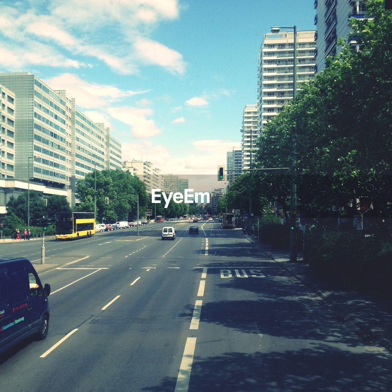 Vehicles On City Street Against Sky
