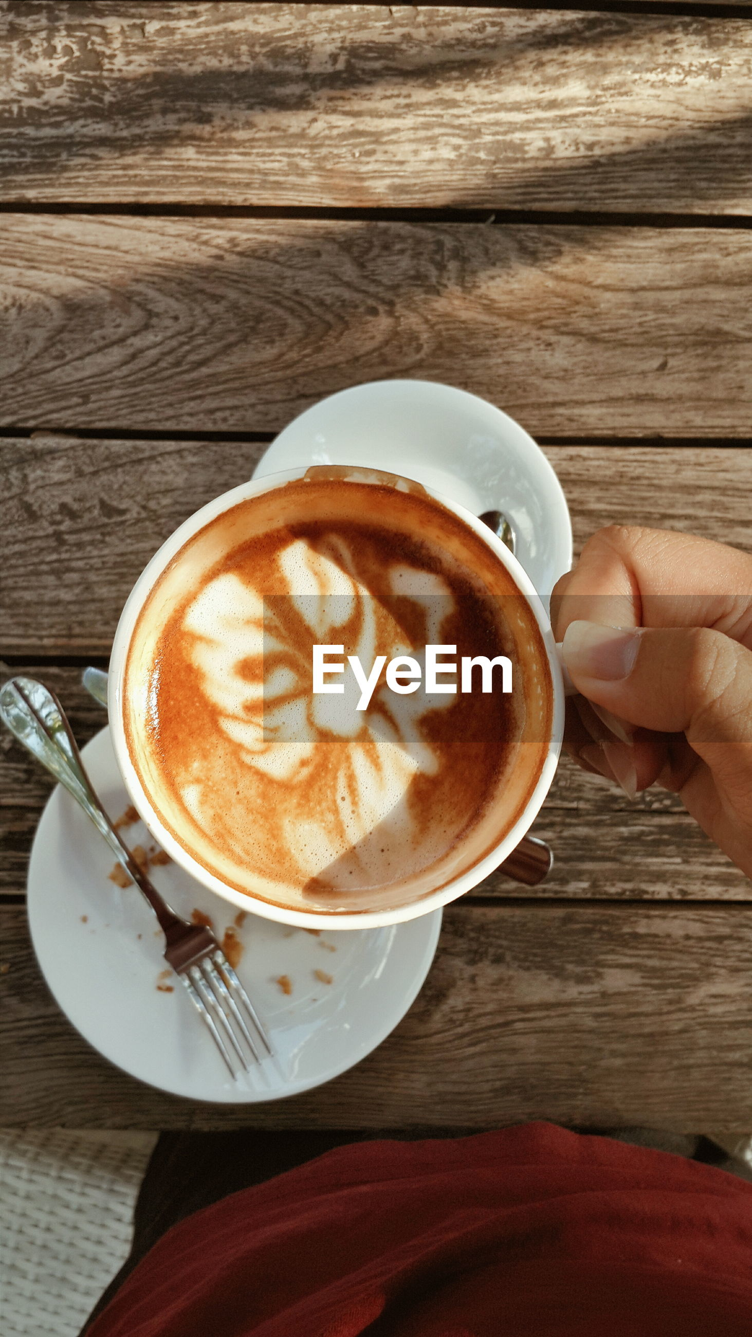 Cropped image of person holding cappuccino in coffee cup