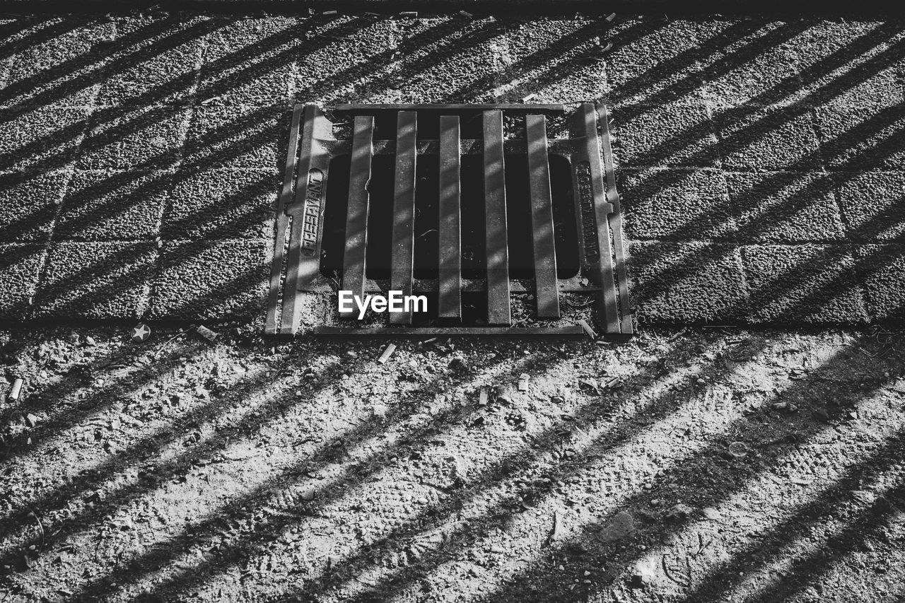 shadow, sunlight, no people, day, metal, pattern, architecture, nature, high angle view, outdoors, built structure, grate, grid, metal grate, close-up, wall - building feature, wall, textured, striped, city, focus on shadow