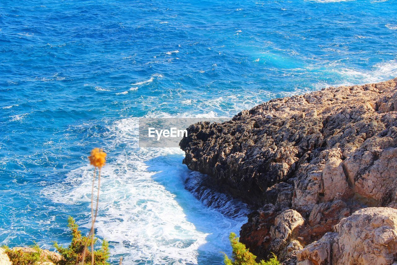 High angle view of waves by rocks
