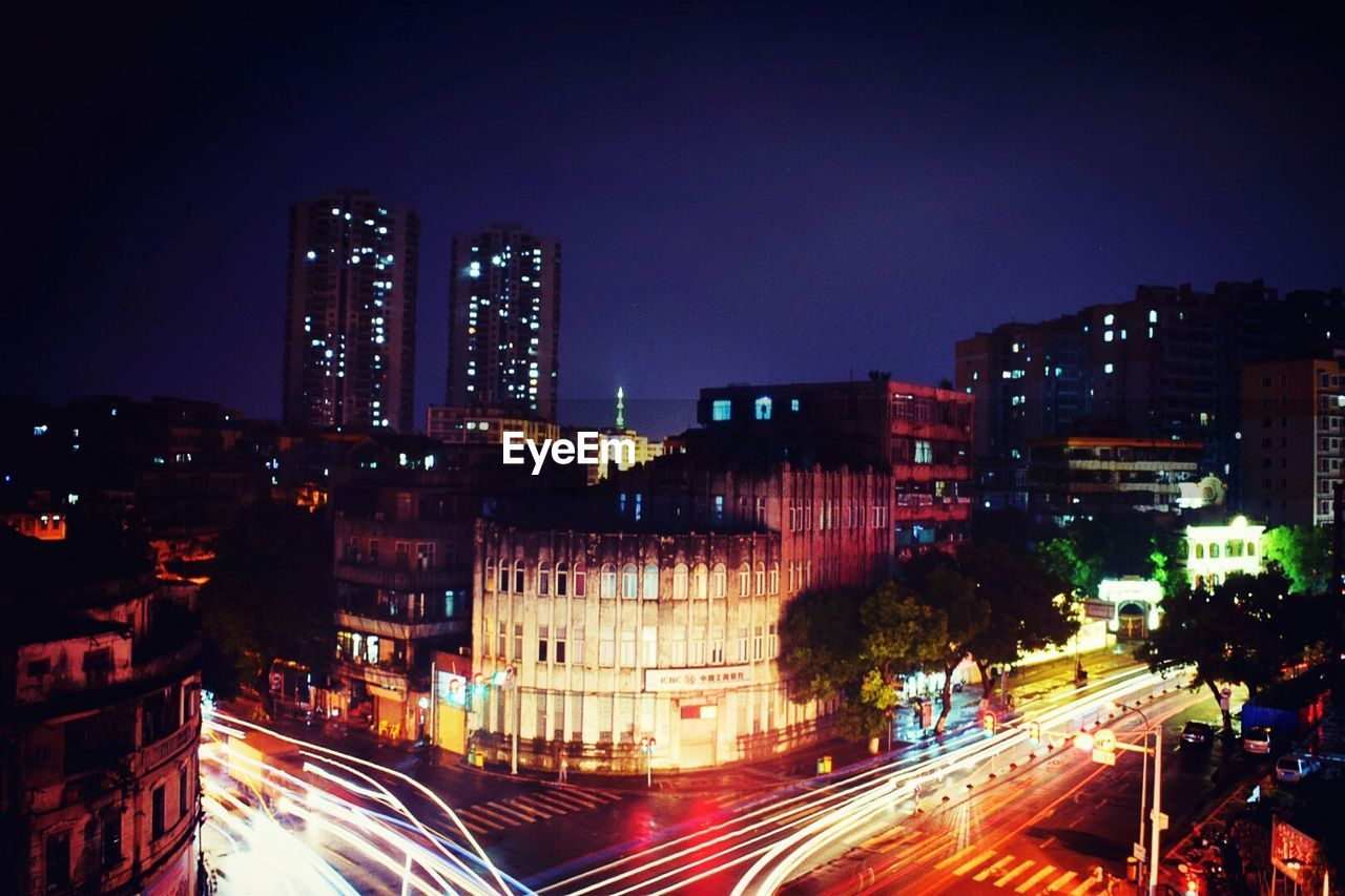 illuminated, night, city, light trail, motion, long exposure, speed, building exterior, blurred motion, architecture, city life, road, street, transportation, traffic, built structure, skyscraper, cityscape, outdoors, street light, urban scene, no people, high street, modern, sky