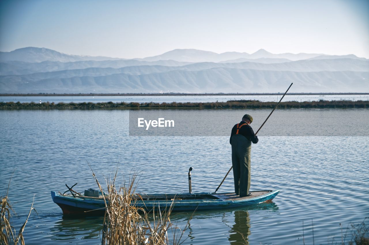 REAR VIEW OF MAN FISHING IN LAKE AGAINST MOUNTAIN