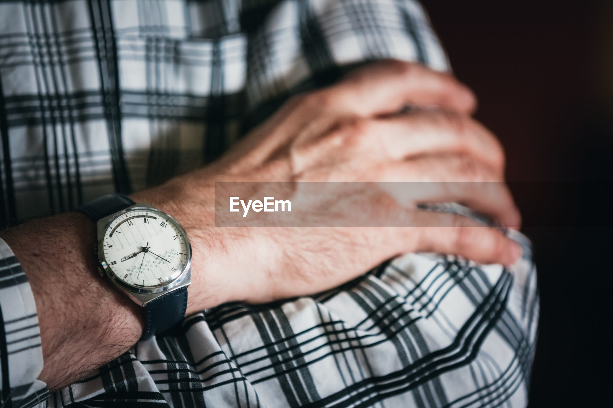 Midsection of man wearing wristwatch