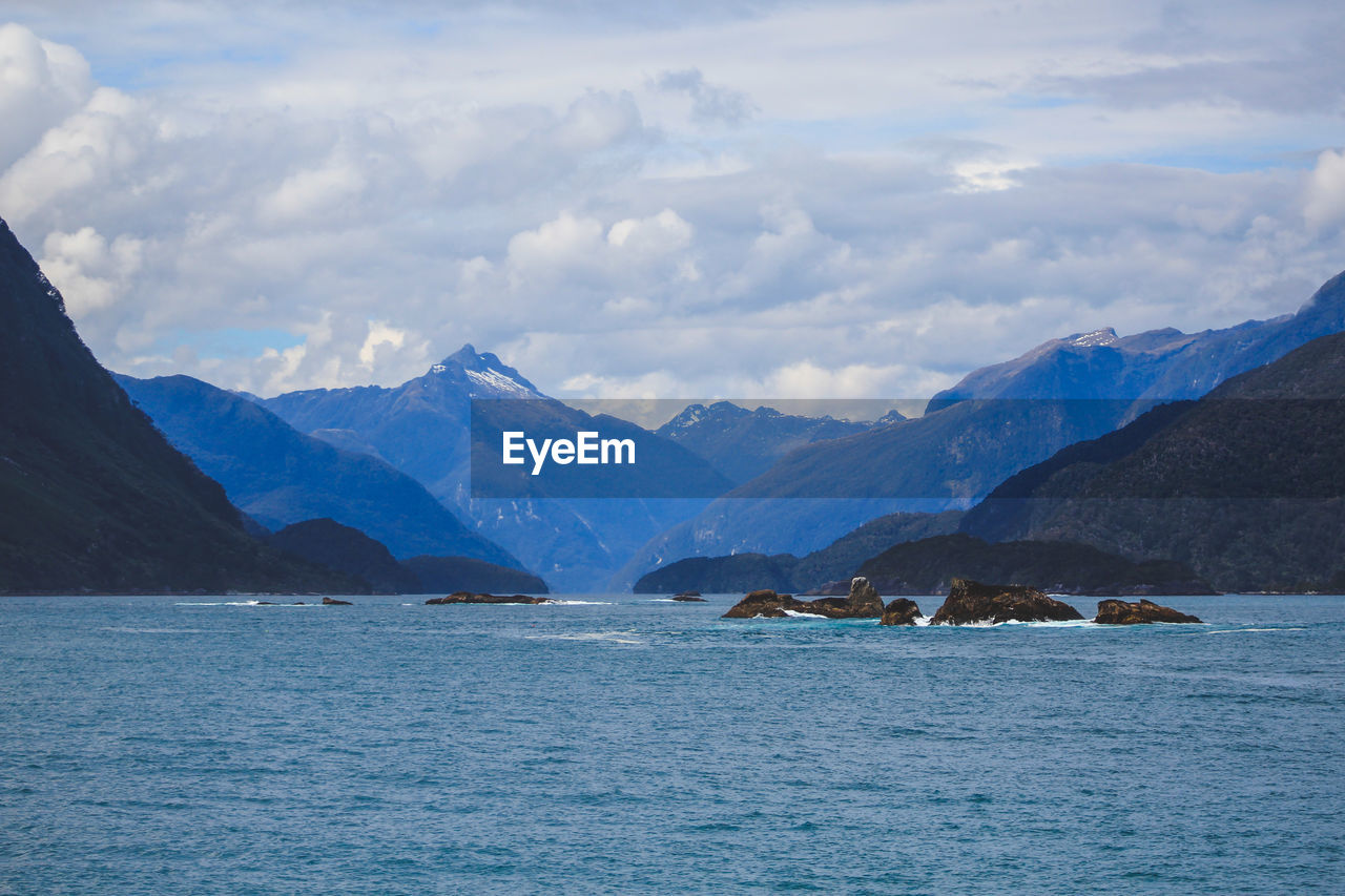mountain, sky, water, cloud - sky, waterfront, scenics - nature, landscape, environment, nature, cold temperature, beauty in nature, sea, tranquil scene, mountain range, wilderness, no people, glacier, tranquility, ice, range, snowcapped mountain, iceberg, mountain peak