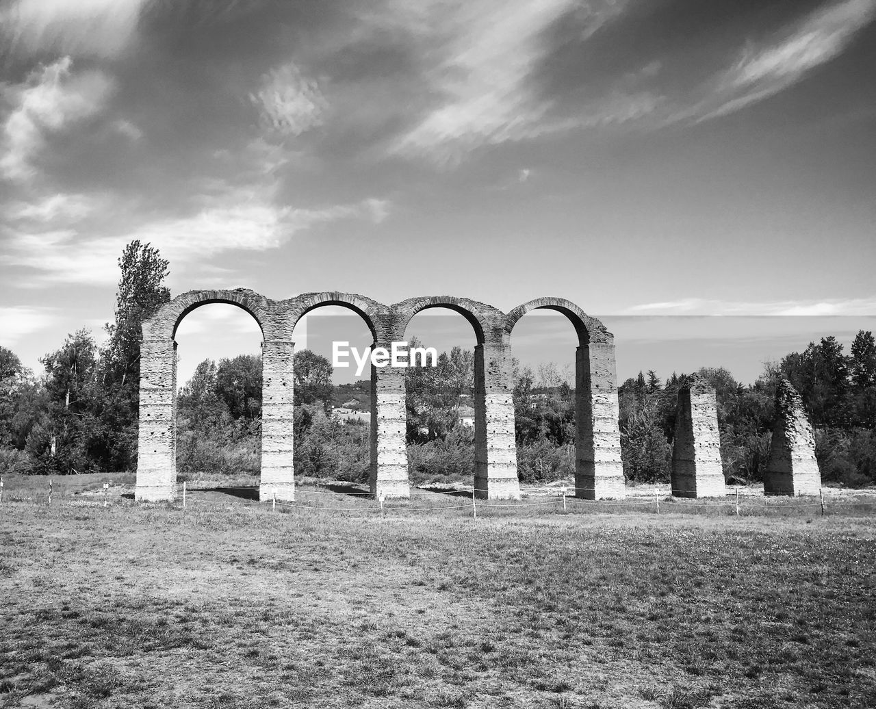 sky, cloud - sky, plant, grass, field, nature, tree, no people, day, architecture, built structure, land, arch, environment, landscape, history, outdoors, tranquility, the past, tranquil scene, architectural column