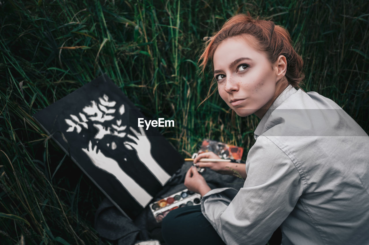 Portrait of young woman using mobile phone in grass