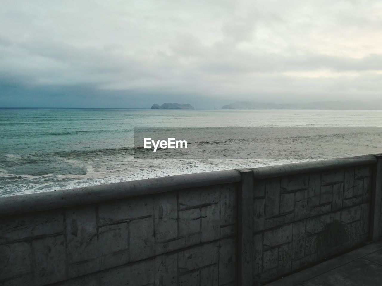 Scenic view of sea against cloudy sky seen from pier
